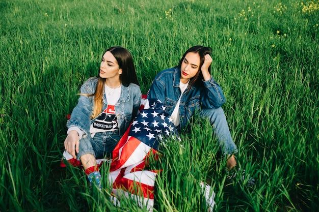 Giovani donne che si siedono sull'erba