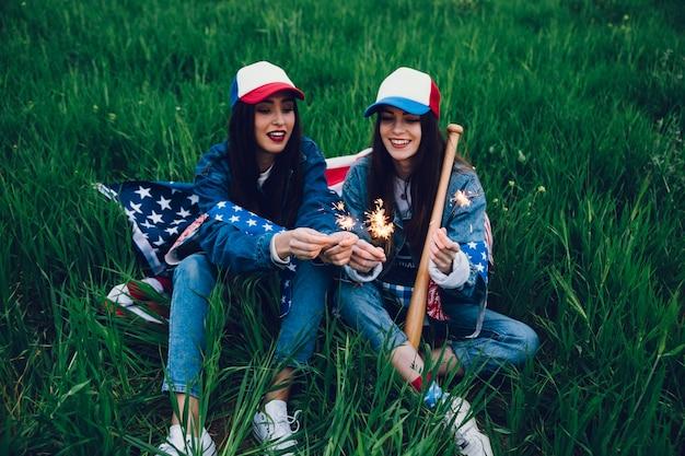 Giovani donne che si siedono sull'erba verde con la bandiera americana
