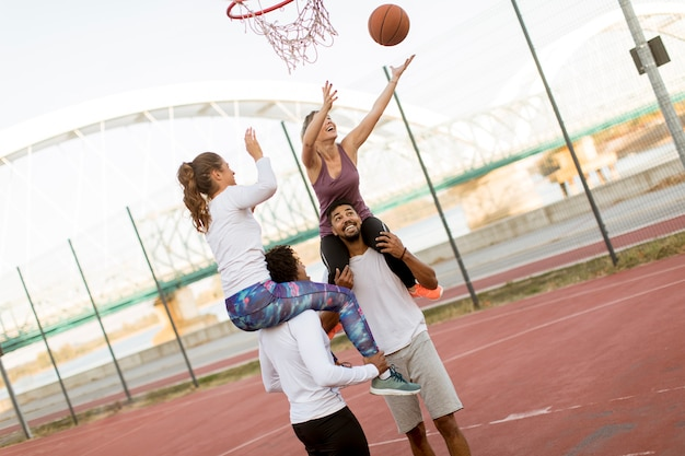 Young women sitting on the men shoulders and holding a basketball at outdoor court