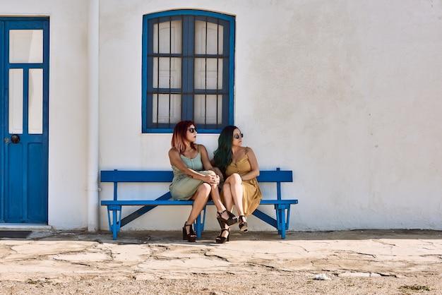 サングラスをかけている青いベンチに座っている若い女性