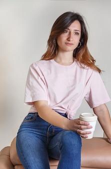 家でソファに座ってコーヒーを飲みながら行く若い女性