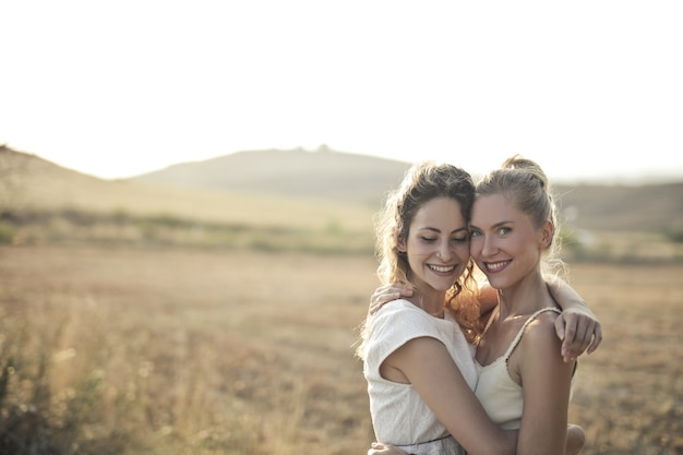 웃 고 분야에서 서로 포옹하는 젊은 여성