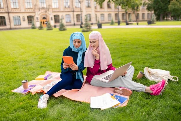 웃 고 젊은 여성. 친구와 화상 채팅을하고 웃는 아름다운 이슬람 젊은 여성