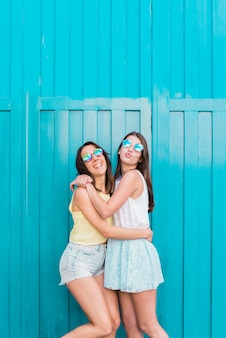 Young women smiling and hugging near blue wall