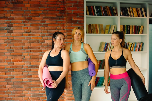 Young women in sportswear with yoga mats are ready for a workout of a brick wall. indoors with empty side space.