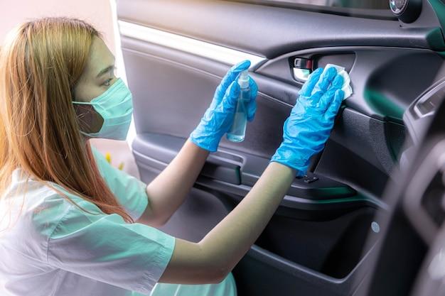 젊은 여성들은 차 문 내부 손잡이를 청소하기 위해 파란색 살균제나 알코올 살균 스프레이를 뿌립니다. 세균 covid-19 및 개인 위생 개념의 오염.