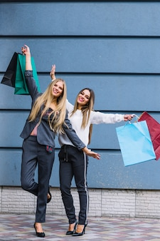 Young women standing in front of wall raising their hands holding shopping bags