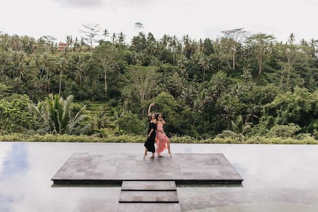 정글 앞에 서있는 젊은 여성. 이국적인 나라의 호수 근처에 아름다운 여성 모델의 야외 전체 길이 샷.