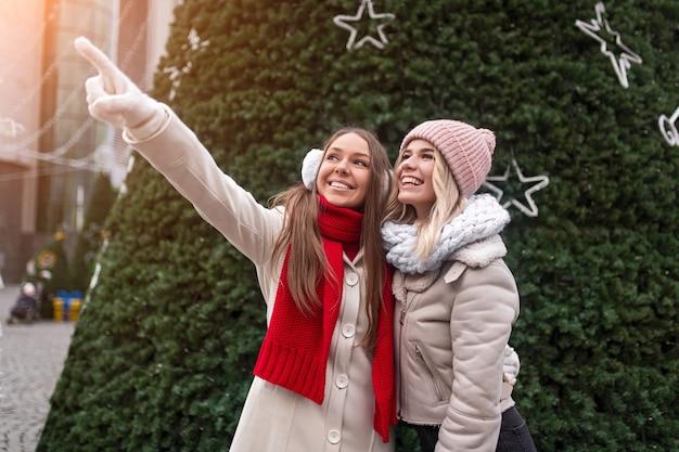 Young women standing near christmas tree
