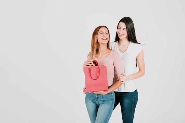 紙袋で立っている若い女性