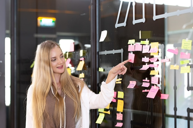 Young women sticking postits on an idea board brainstorming and organizing whiteboard chalkboard
