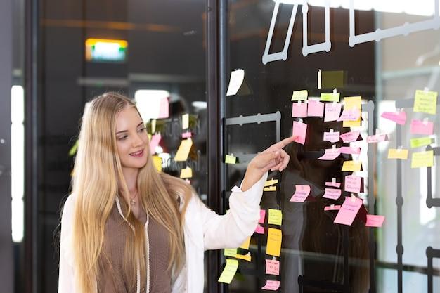 アイデアボードに付箋を貼る若い女性ホワイトボード黒板のブレーンストーミングと整理