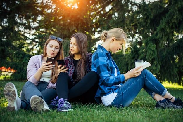 木の中で緑の芝生の上の若い女性学生