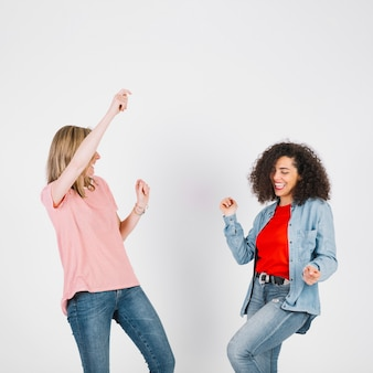 Young women in stylish outfits dancing