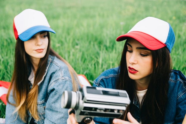 Young women in summer field sitting in colored caps