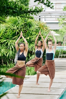 Young women in swimsuits and towel standing in tree asana when practicing yoga before swimming in pool