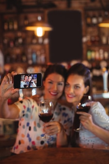 赤ワインを飲みながら携帯電話から自分撮りを取る若い女性