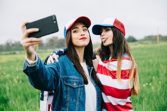 Young women taking photo on phone outside