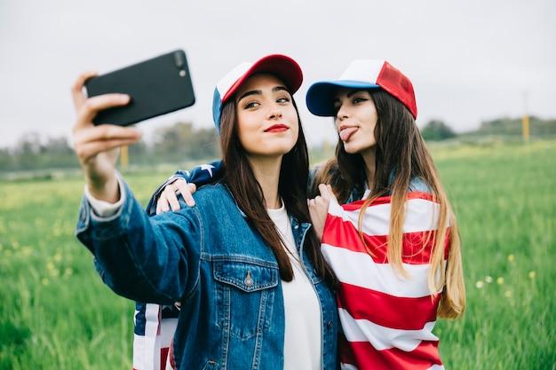 Молодые женщины фотографируют по телефону на улице