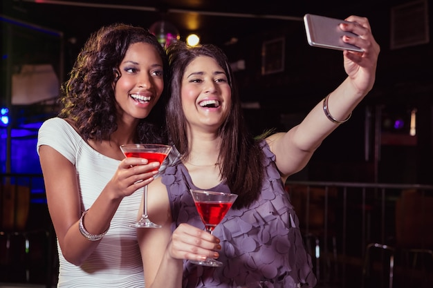 Young women taking a selfie while having a cocktail drink in bar