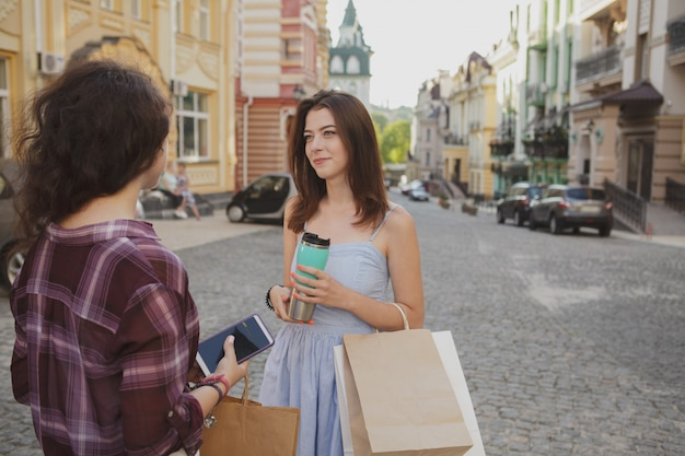 Young women talking on the city streets after shopping, copy space