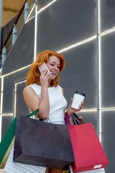 Молодые женщины разговаривают по телефону с пакетами покупки в современном торговом центре. торговая концепция. черная пятница концепция. счастливые женщины. холдинг пакеты.