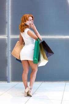 현대 몰에서 패키지 쇼핑과 전화 통화하는 젊은 여성