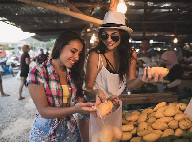 Young women talking while buy exotic fruits on tropical market happy smiling girld tourists in asian