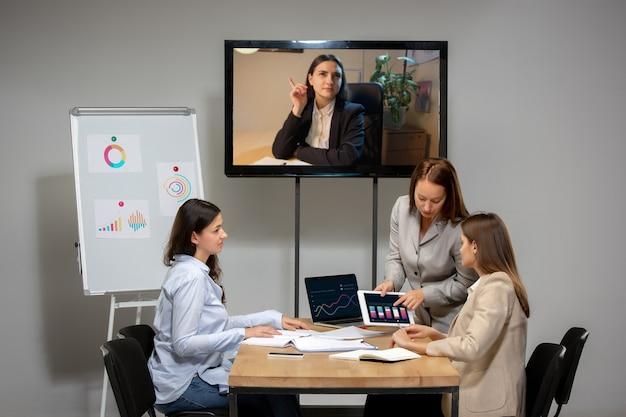 オフィスや居間で同僚とビデオ会議中に働いて話している若い女性