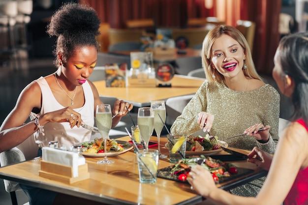 Молодая женщина. три успешные молодые модницы чувствуют себя взволнованными за ужином вместе