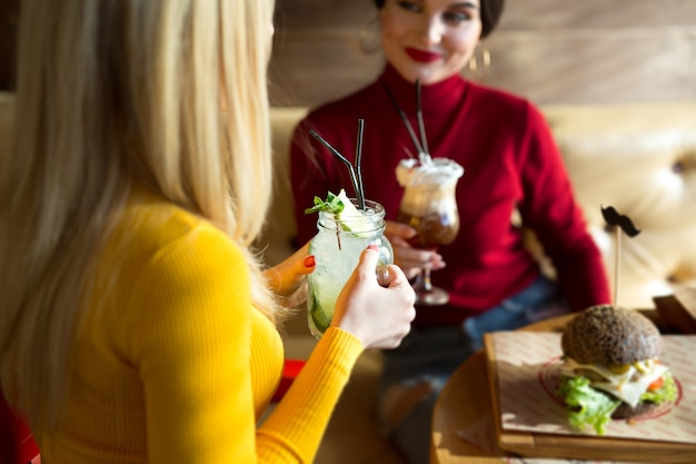 Молодые женщины жарят бокалы для коктейлей