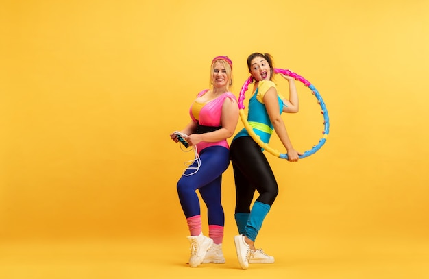 黄色の壁でトレーニングする若い女性