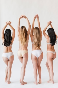 Young women in underwear standing with raised hands