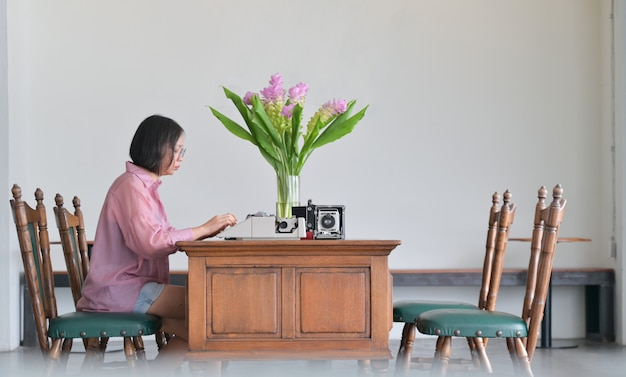 젊은 여성들은 고전적인 사무실에서 오래된 타자기를 사용합니다.