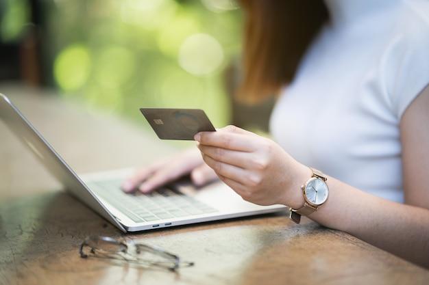 노트북 및 신용 카드 온라인 쇼핑을 사용하는 젊은 여성, 전자 상거래 개념