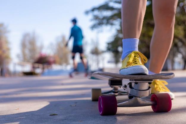 スケートボードで熱帯のビーチの近くの脇道を歩いている若い女性。