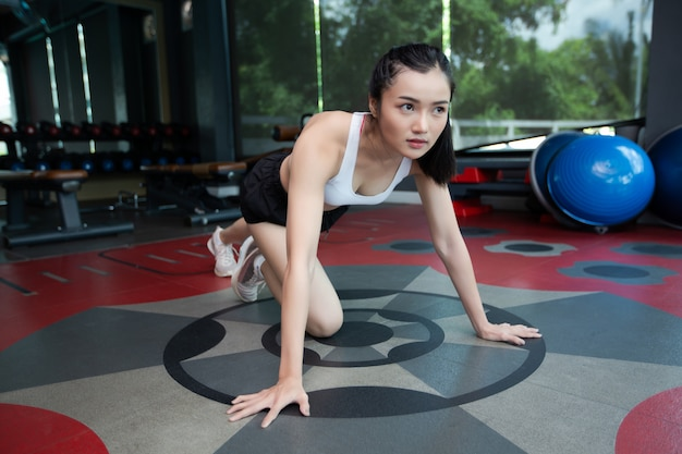 Young women warms up before exercising by pushing the floor and bending his knees in gym.