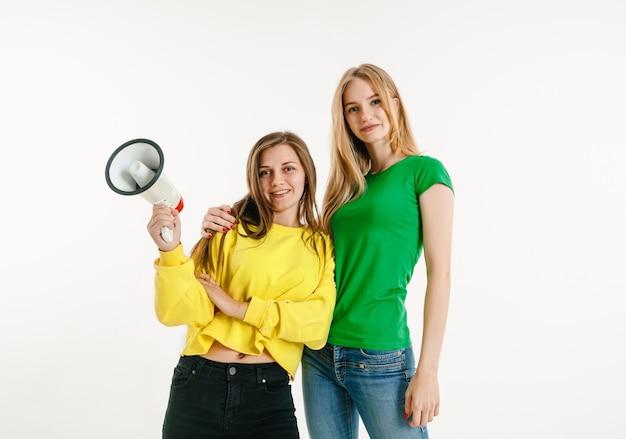 白い壁にlgbtの旗の色を着た若い女性。明るいシャツを着た白人モデル。