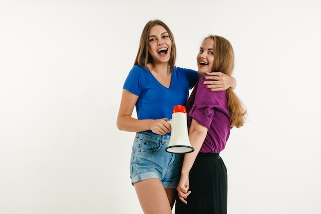 Young women weared in lgbt flag colors on white wall. models in bright shirts