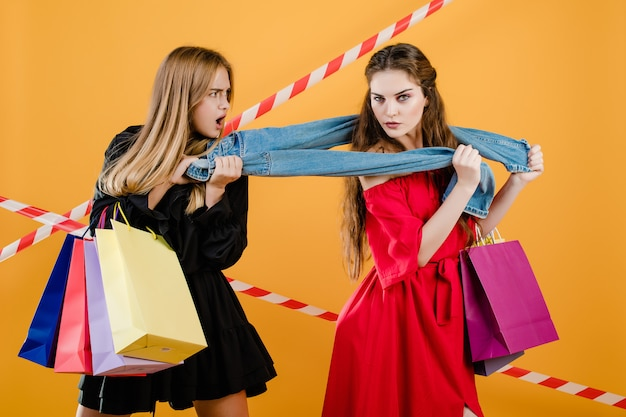 Young women wearing dresses fighting over pair of jeans with shopping bags isolated over yellow
