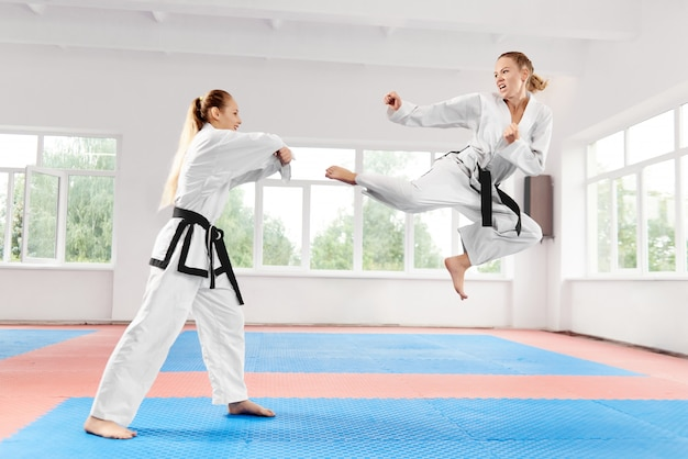 Young women wearing in kimono and black belt training karate martial arts.