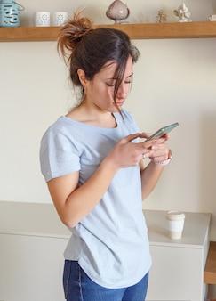 携帯電話を使用して水色のtシャツを着ている若い女性