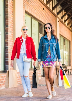 Young women with bags going on shopping street
