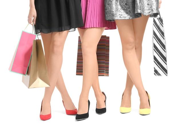 Young women with beautiful legs holding shopping bags