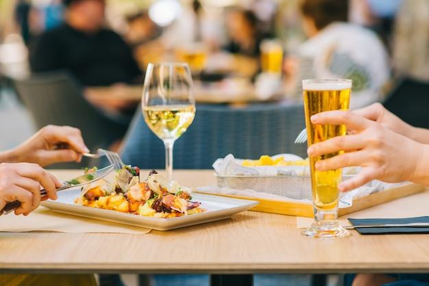 Молодые женщины с пивом и вином и едят на террасе - две девушки вместе обедают в ресторане