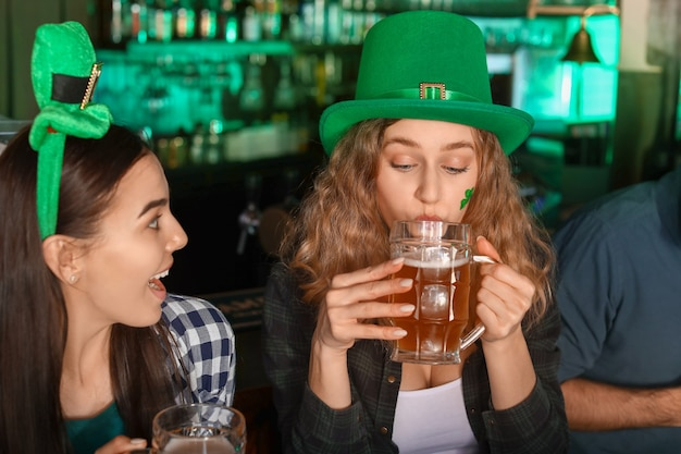 Young women with beer celebrating st. patrick's day in pub