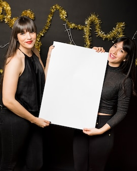 Young women with canvas near tinsel