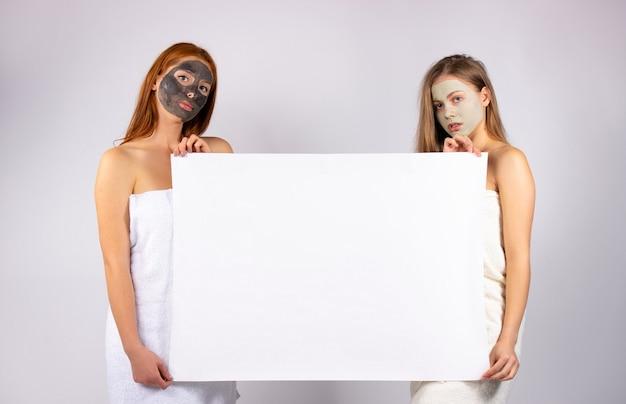 広告のために手に顔と大きな紙を持つ若い女性