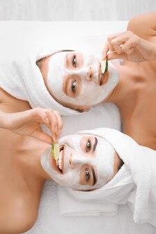 Молодые женщины с масками для лица и ломтиками огурца в спа-салоне