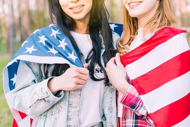 Giovani donne con la bandiera che abbraccia